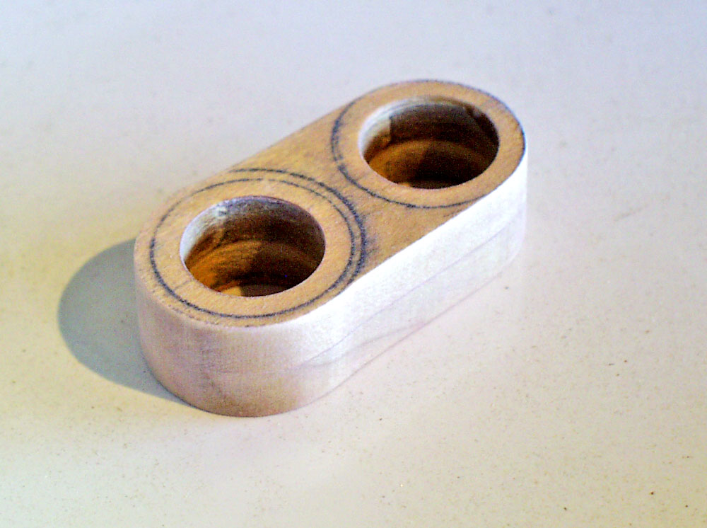 The bracket that holds the pump tube and barrel in place was made from two pieces of 1/4″ poplar glued together.