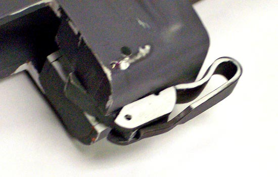 The latch in position shows how the latch rotates and, with pressure from a hidden spring, locks the magazine in place. The folding handle flips down and then moves the latch away from the magazine, allowing it to be removed.