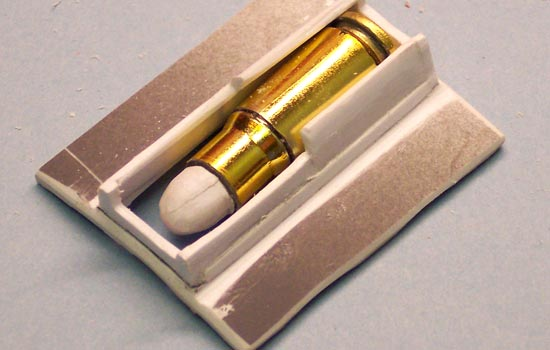 The bracket will mount over the drum opening and allow the bullets to feed into the gun.