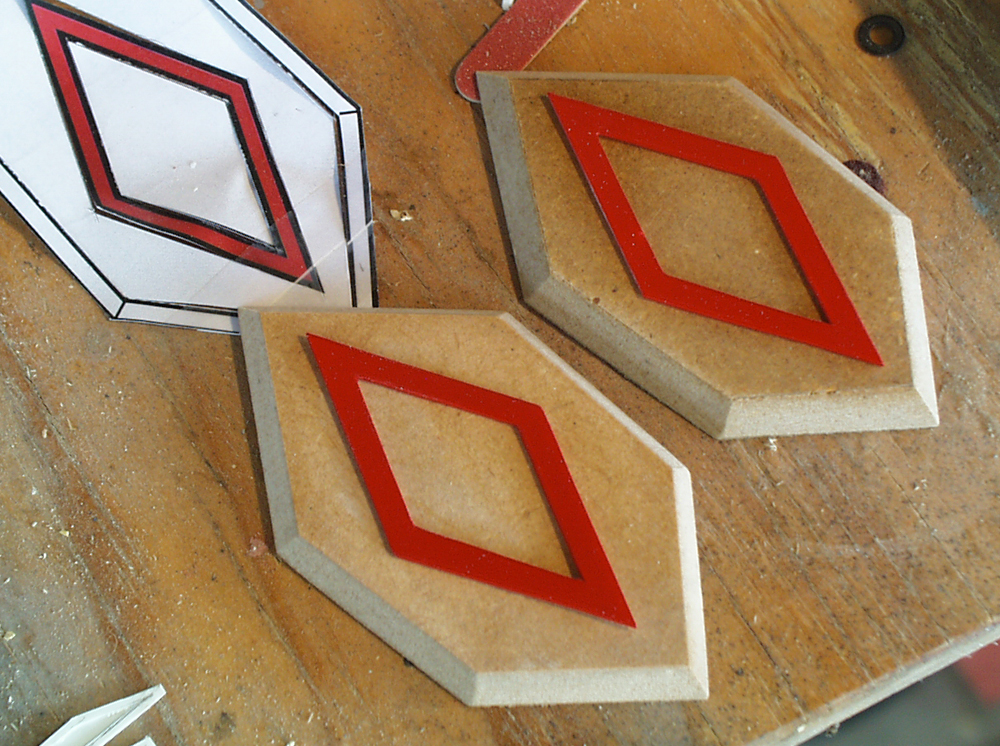 I cut the recess polygons from 1/4″ MDF and used styrene to make the diamond details.