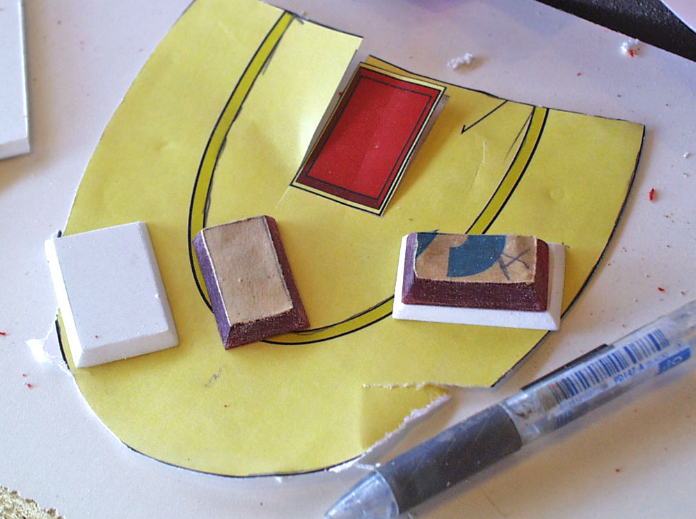 The hilt gems were cut from 1/4″ red acrylic. The base was cut from thick styrene.