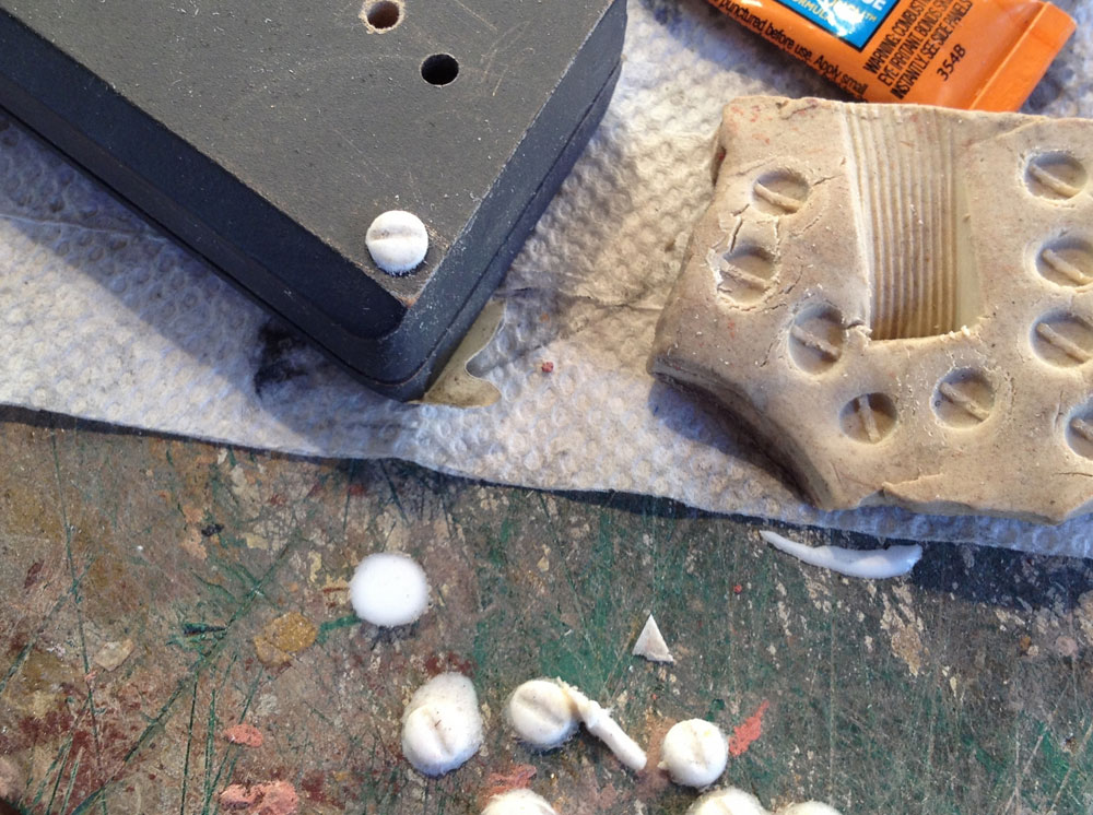 I needed round headed screws for the base of the grip and OF COURSE there was only one in my hardware bins. I guess I was too lazy to go to the hardware store to buy three more so I made a quick mold of the one in clay and dumped resin into it to make plastic copies.