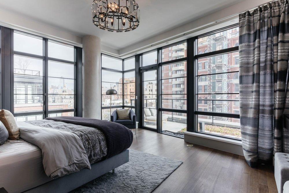 Bedroom with floor to ceiling steel frame windows