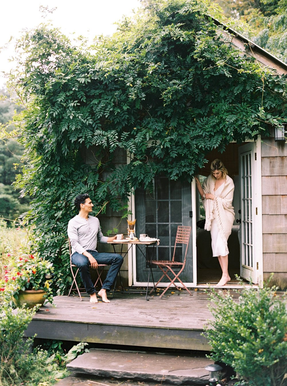 A male and female model posing on front porch of wooden tiny house