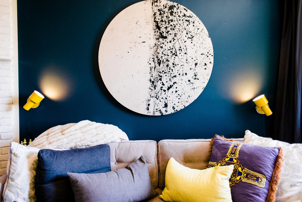 Sofa with round abstract art hanging above