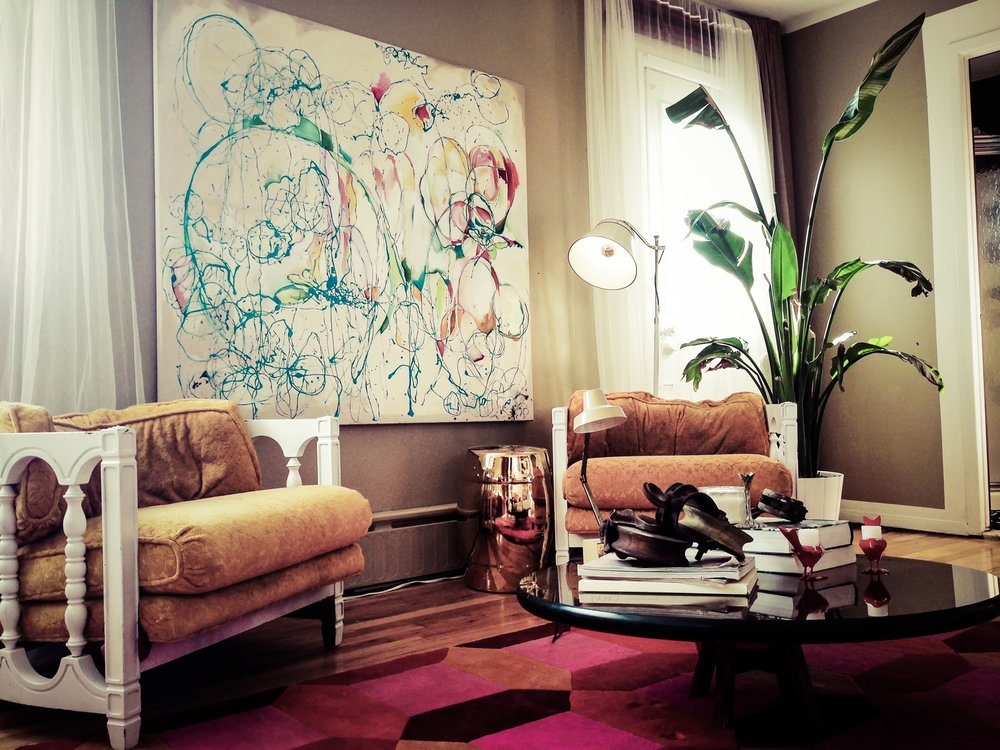 Sitting room area with abstract art hanging on wall