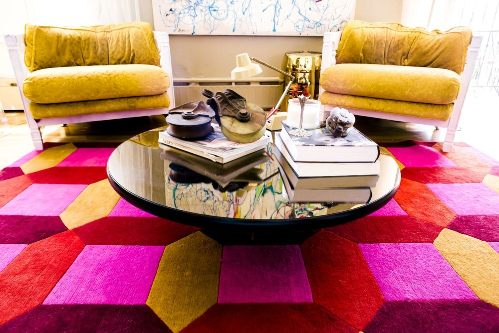 Coffee table on large colorful rug