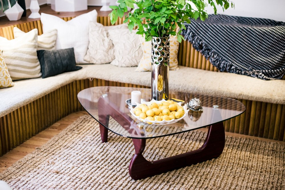 Triangular glass coffee table with dish of fruit