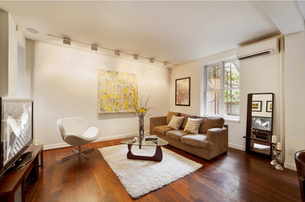 Sitting room space with art mounted on wall with gallery lighting