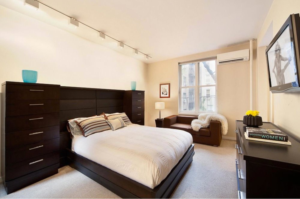 Modern bedroom with large wooden bed console with drawers