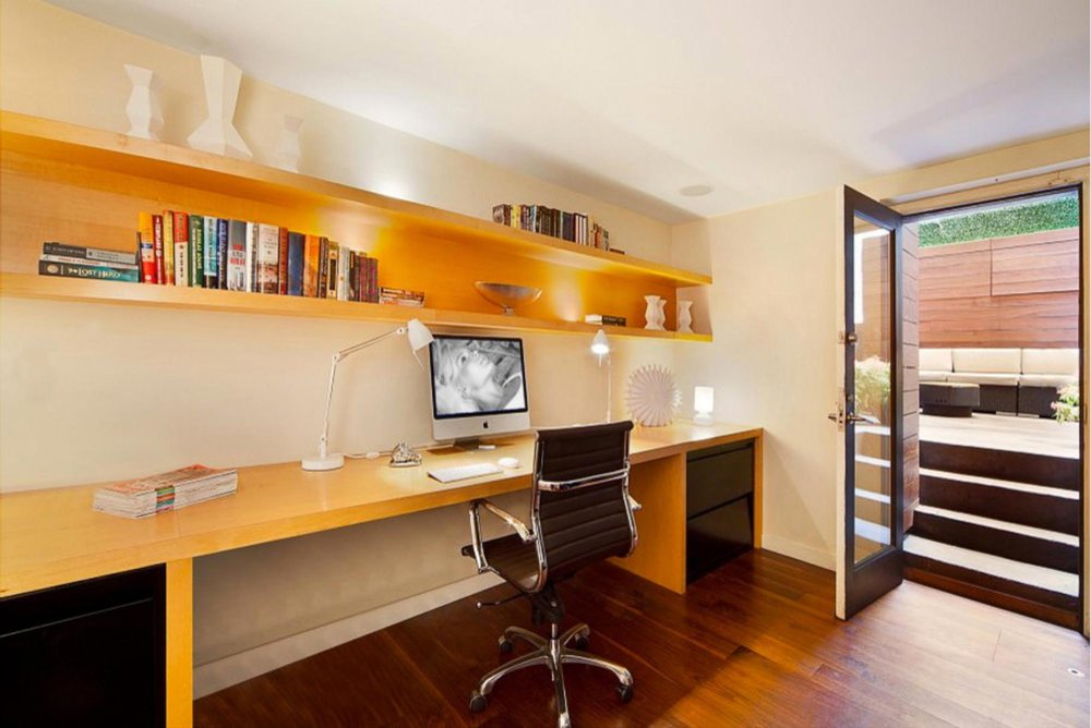Office space with custom full width wooden desk and floating shelf
