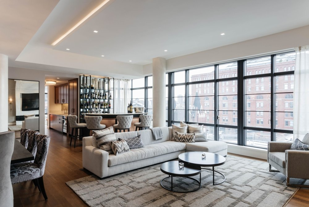 Open concept living room space with floor to ceiling steel frame windows
