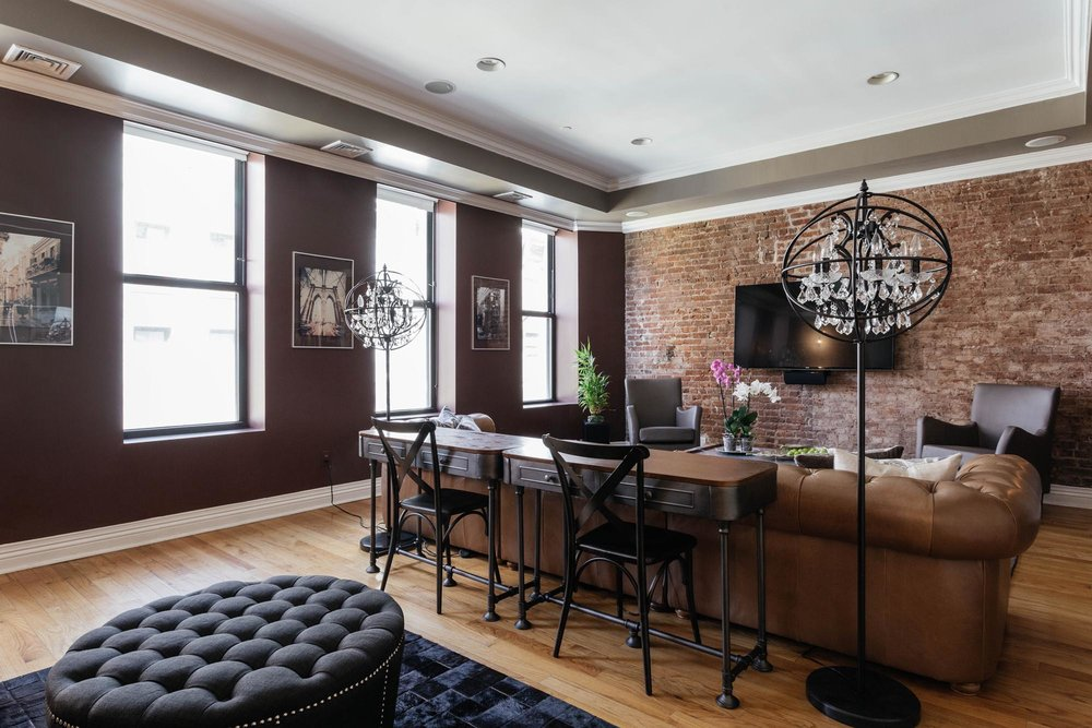Open concept living room space with rich dark furnishings and brick wall