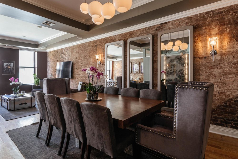 Dining room area with long wooden table and brick wall with hanging mirrors