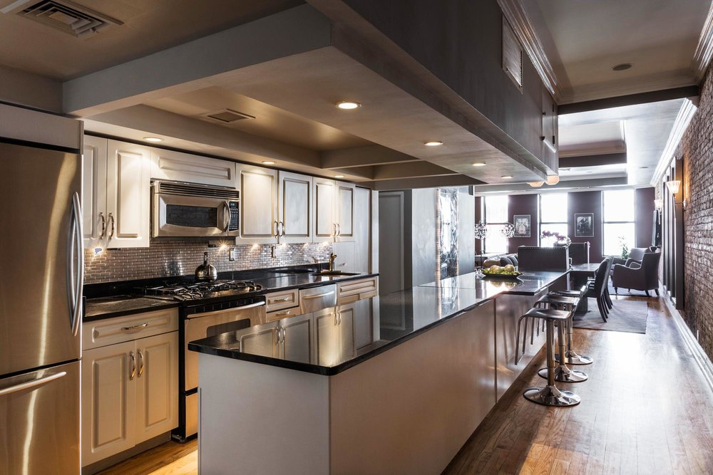 Long kitchen island with black marble counter and high bar stools