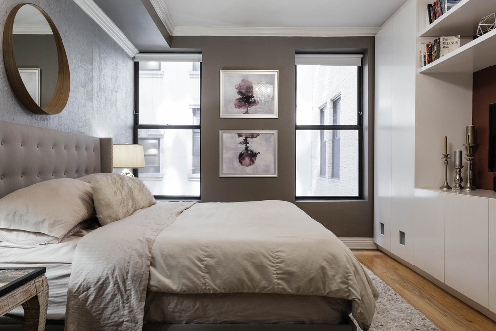 Light colored bedroom with round mirror above bed