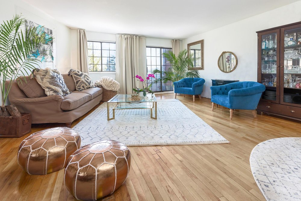 Bright open concept living room space with bright blue plush seats