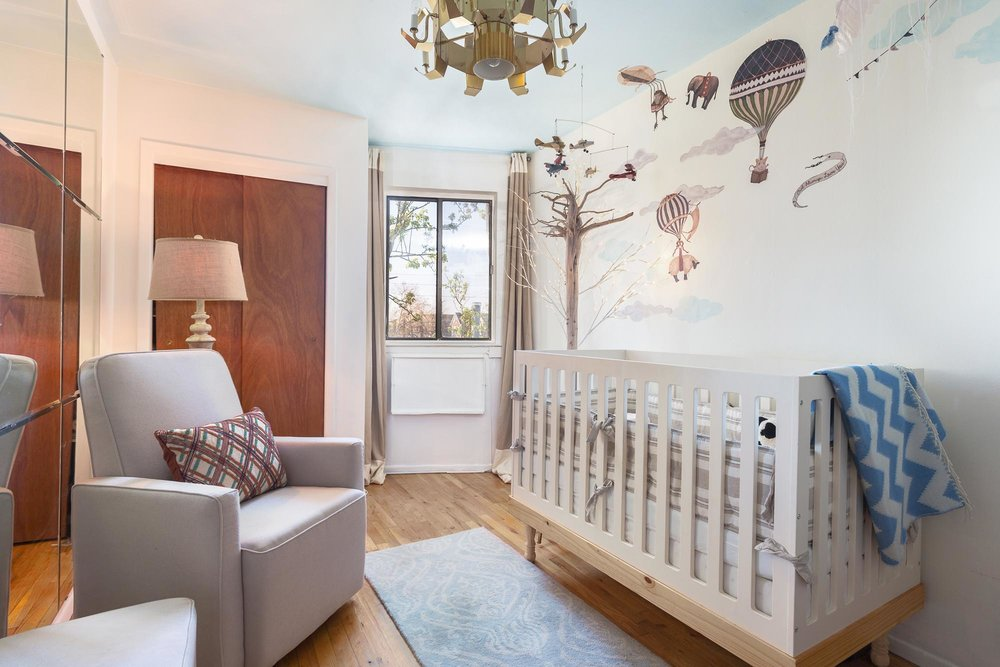 Baby crib with hot air balloon decals on wall