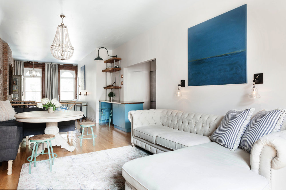 Blue painting hanging over soft white sectional sofa