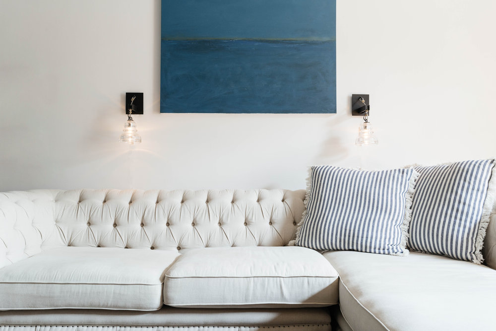 Blue painting hanging over soft with sectional sofa