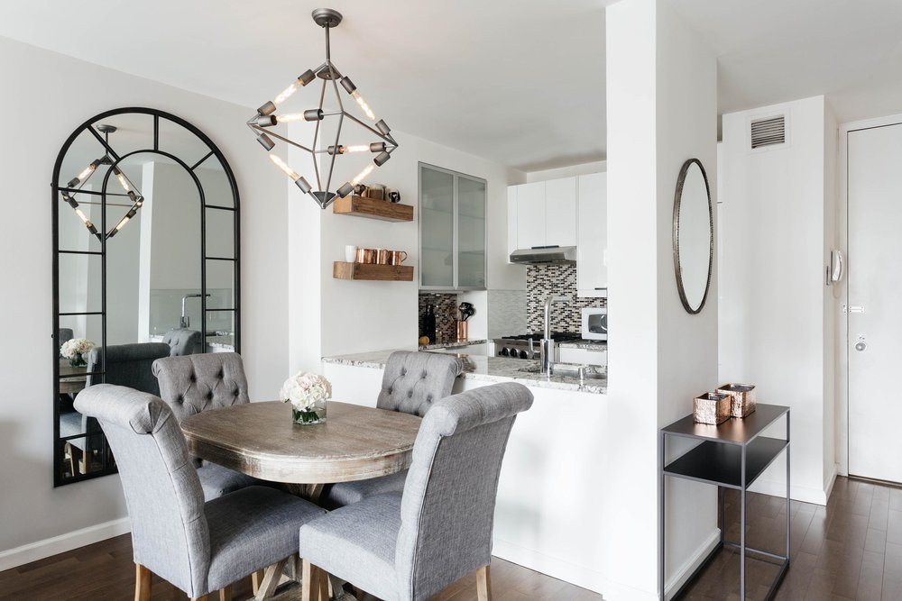 Breakfast nook area with round wooden table and soft grey chairs