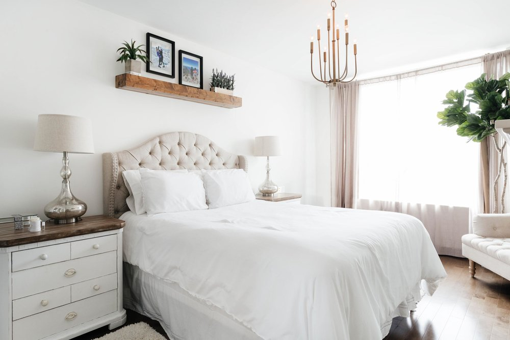 Bright bed room with wooden shelf hanging above bed