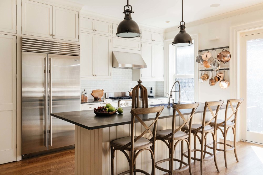 Rustic kitchen with chairs lining a central kitchen island