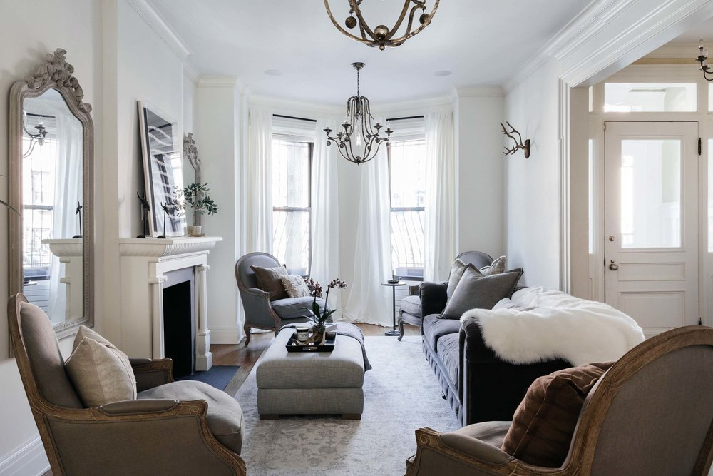 Bright living room area with plush seating and flowers on an ottoman