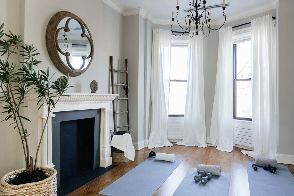 Bright living room area with yoga mats and weights resting on floor