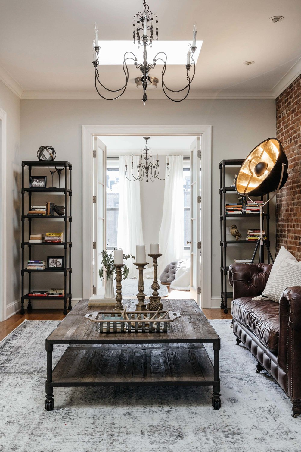 Rustic square coffee table and an antique standing lamp in the corner of the room
