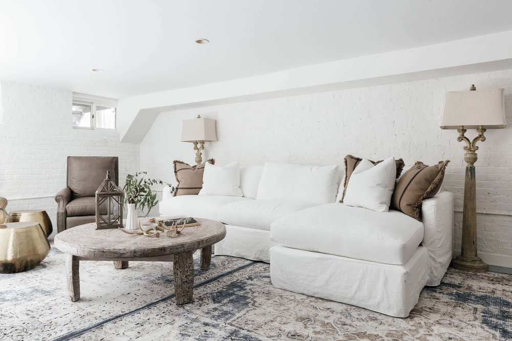 Bright basement seating area with white sectional sofa and rustic brown coffee table