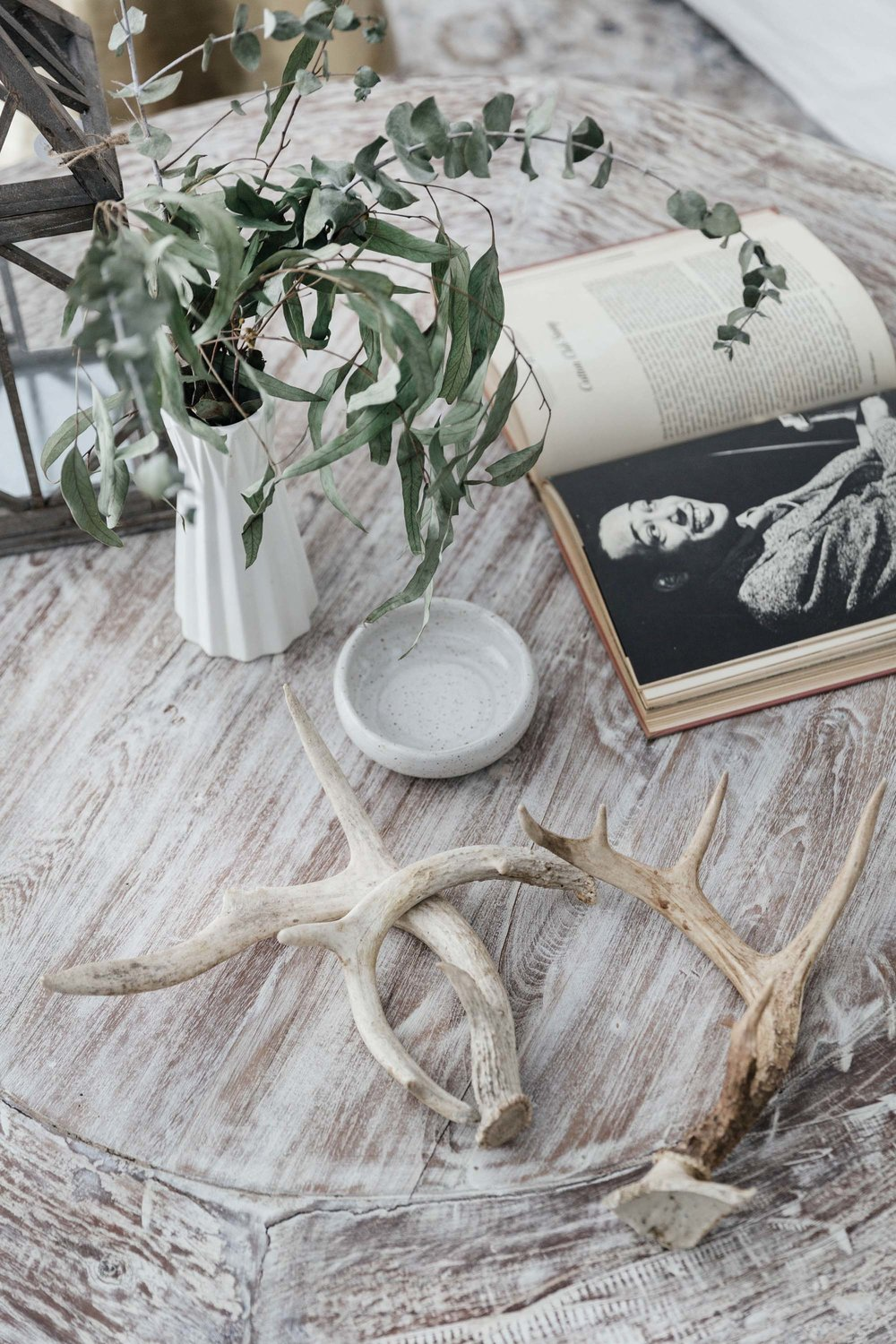 Distressed wooden coffee table with a vase of flowers and antlers