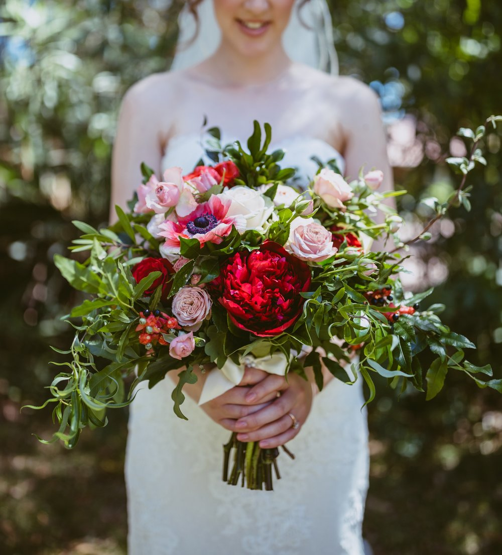 Natural hand tied Bridal Bouquet with a pop of red.