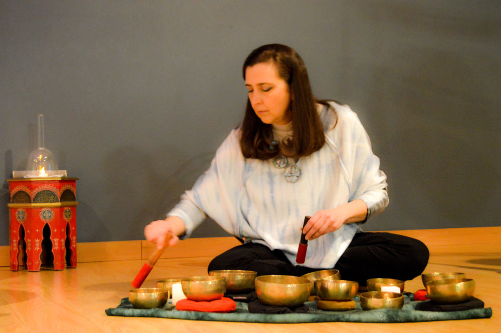 """Amy Hamilton - Greetings! I'm Amy Hamilton, Founder and Sound Guide for SoundScapes Tulsa.The gifting of a Tibetan bowl and a weekend workshop learning how to play crystal bowls activated my awareness and interest in working with sound healing instruments for restorative and healing purposes.SoundScapes Tulsa was officially """"born"""" at the 2015 I AM yoga festival where I had the opportunity to share my 1st public SoundScape Experience*. Over the last few years sharing these experiences and working Intentionally with Sound has become a passion, and dare I say… an addiction! I love it!I have shared public SoundScapes at Zen Body Yoga, I AM Yoga Festivals, H2Oasis Float Center, I AM Yoga Studio, a Big OM retreat, and Yoga Groove. I also offer 1 on 1 (or couples) and small group Sound Bath sessions in my home Sound Studio. I completed my Level 1 Foundational Diploma in Sound Therapy in 2015 and I'm currently working on my Level 2 Certification as an Integral Sound Healing Therapist.My full time/day time gig is working at Tulsa Tech as a Client Services/Project Coordinator in the Business Industry Services department. I office at 36 Degrees North (which is a totally awesome place) and I get to coordinate and facilitate low cost and high quality training opportunities to Tulsa's Non-Profit community. I'm one lucky girl to get to do this for my FT job!In addition to SoundScapes Tulsa, other """"Side Hustles"""" I have launched include Founder/Guide of the Community of the Sacred Wheel – a Womyn's Circle, and Founder/Member of Harmonyc Fuzion – a trio sharing """"music that matters."""""""