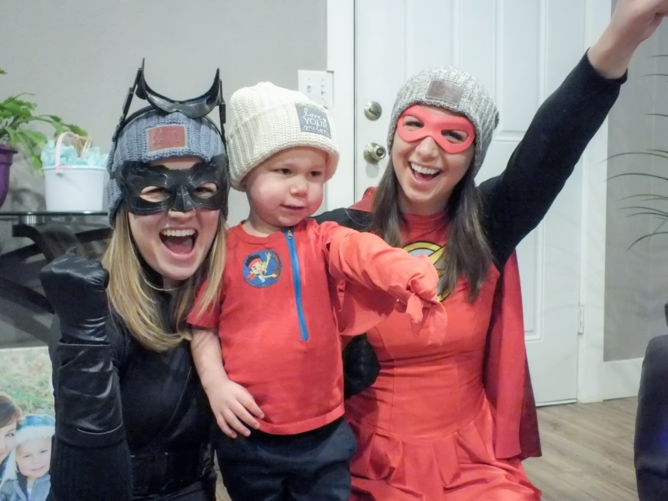 Boise State students Tristin Harris and Aspen Phillips, dressed as superheroes, visit with 3-year-old cancer patient Reece Harper as part of a Love Your Melon home visitation. Photo courtesy of Aspen Phillips
