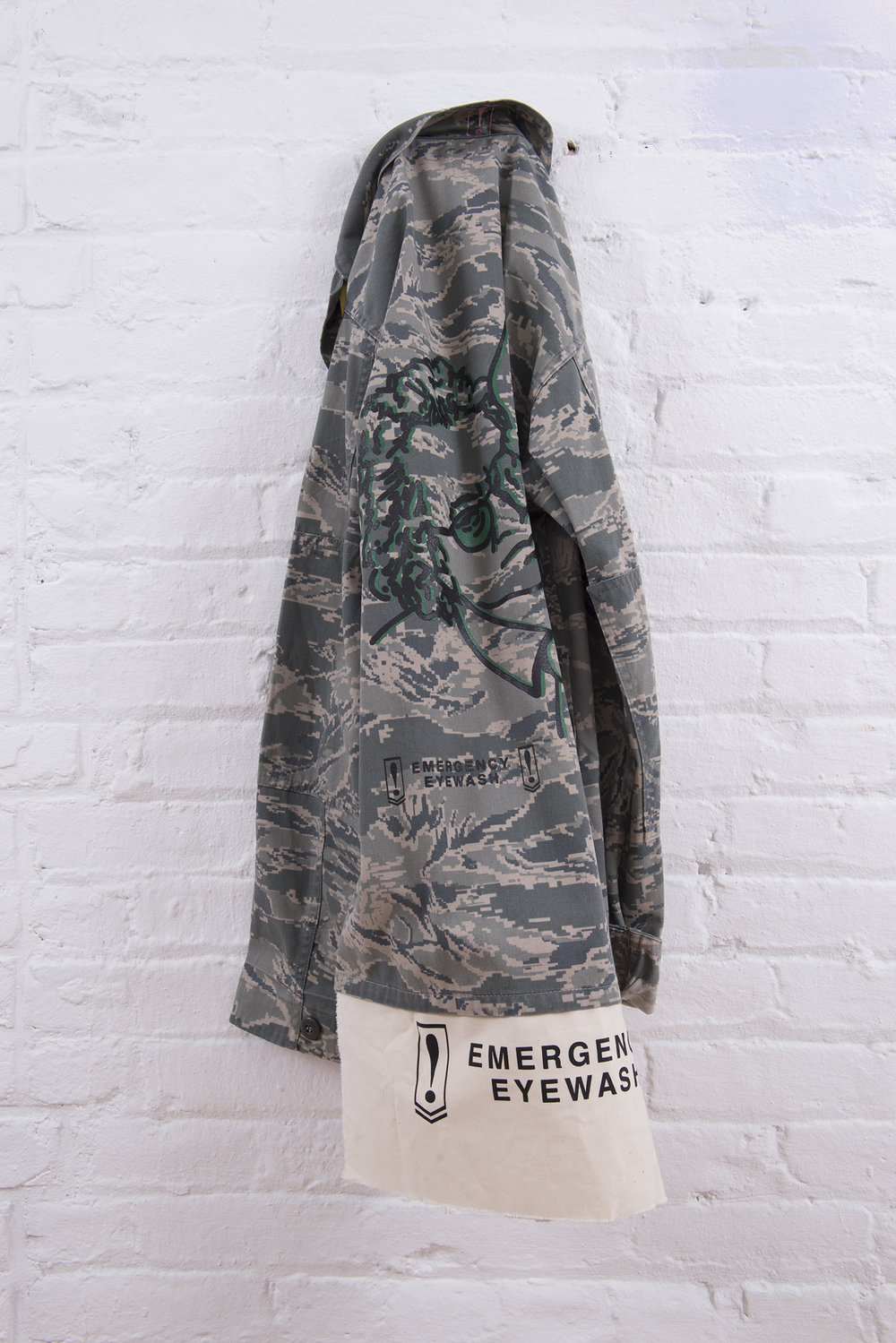 Ahem. Carol Szymanski & Xiaofu Wang. 2018. Vintage military camouflage jacket with Emergency Eyewash patches and silkscreen images