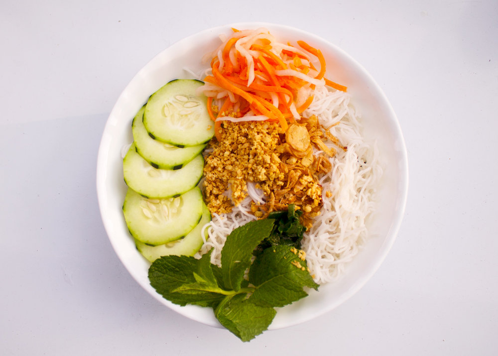 Rice vermicelli salad topped with lettuce, cucumber, mint leaves, and roasted peanuts