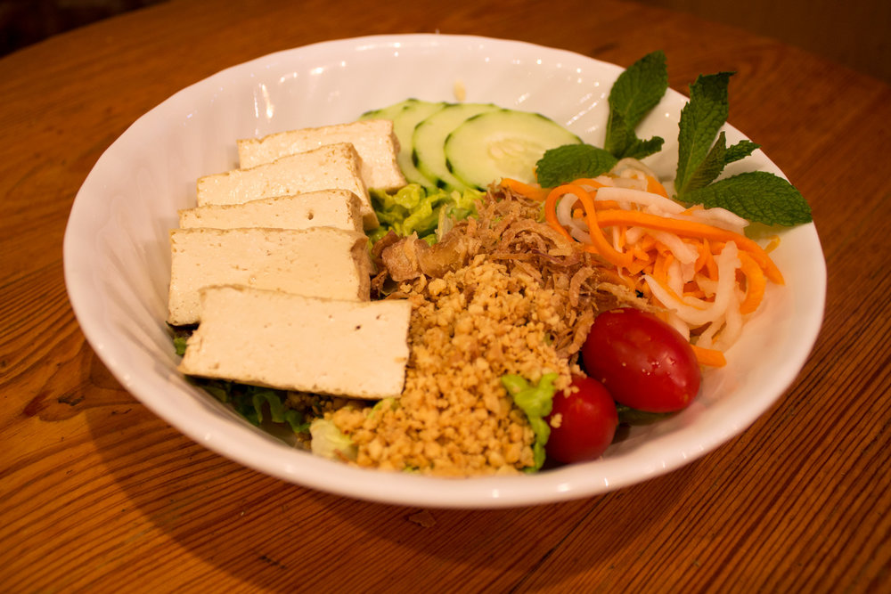 Tofu green salad topped with lettuce, tomato, cucumber, julienne carrots, daikon radish, mint leaves, and roasted peanuts