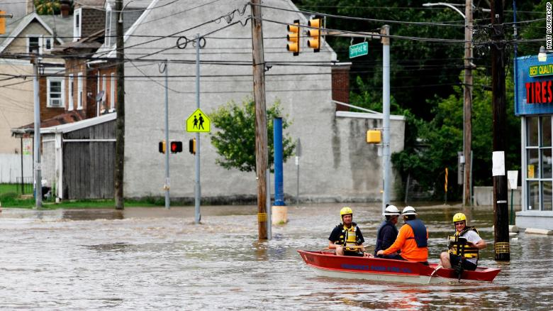 First responders make their way through floodwaters in Darby, Pennsylvania, on Monday.