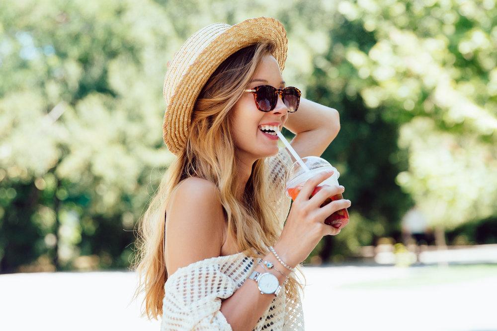Joyful woman drinking a cocktail, standing outdoors
