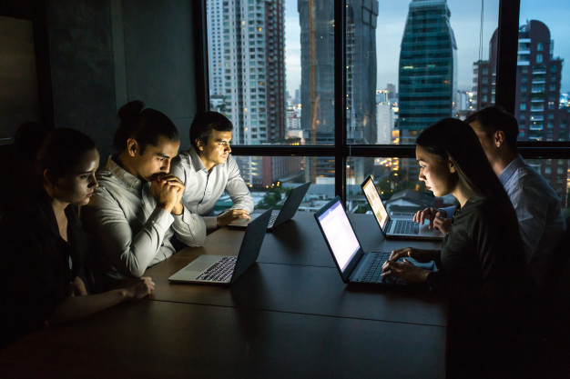 business-team-working-late-night-with-lights-off-computers-laptop-screen-light_42892-103.jpg