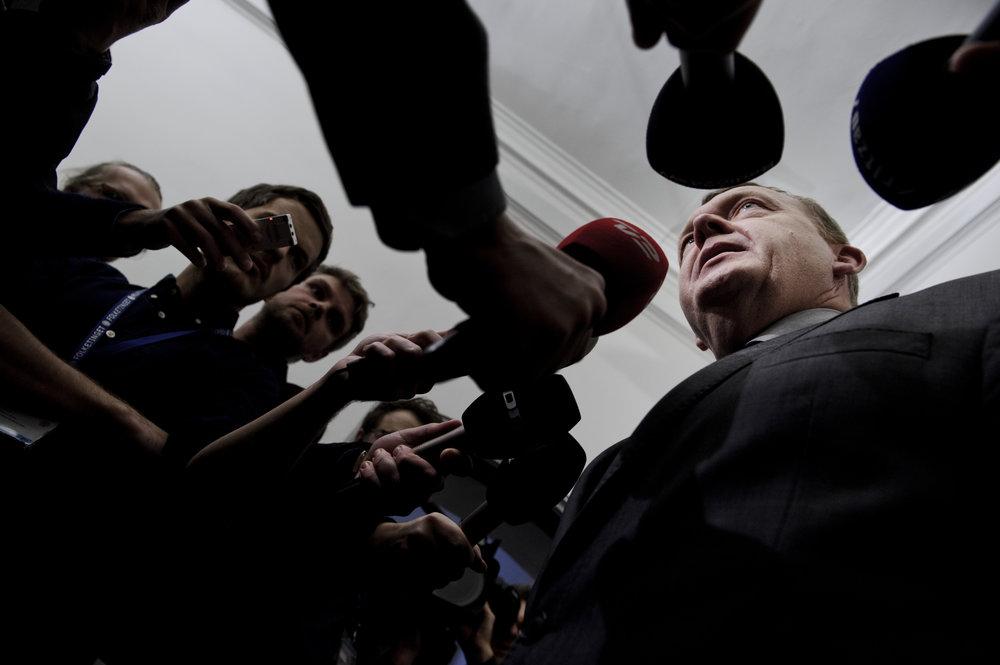 … skatteforhandlingerne havde stået på i mange timer, og pressepoolen var fyldt til bristepunktet af ivrige fotografer og kamerafolk. Eneste plads var et skud fra jorden med mikrofoner, som dannede en ramme om Lars Løkke Rasmussen.