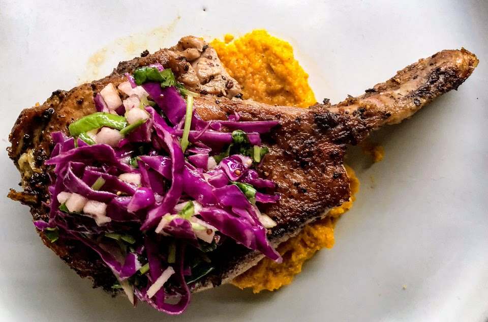 Plated spring bone-in Pork loin chop with carrot puree and apple slaw for spring.jpg