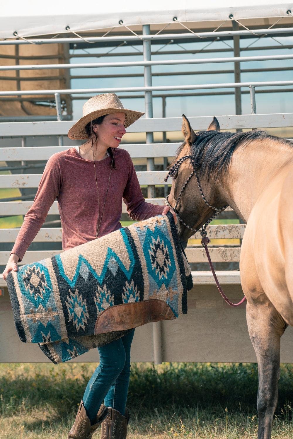 Melissa DiNino saddling a horse in Montana's Centennial Valley.