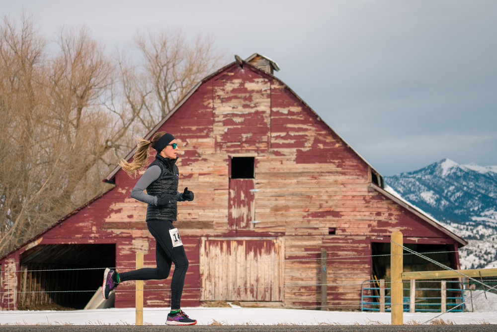 Striding it out past an old, red barn during Bozeman Running Co.'s racing of the Bear near Bozeman, Montana.