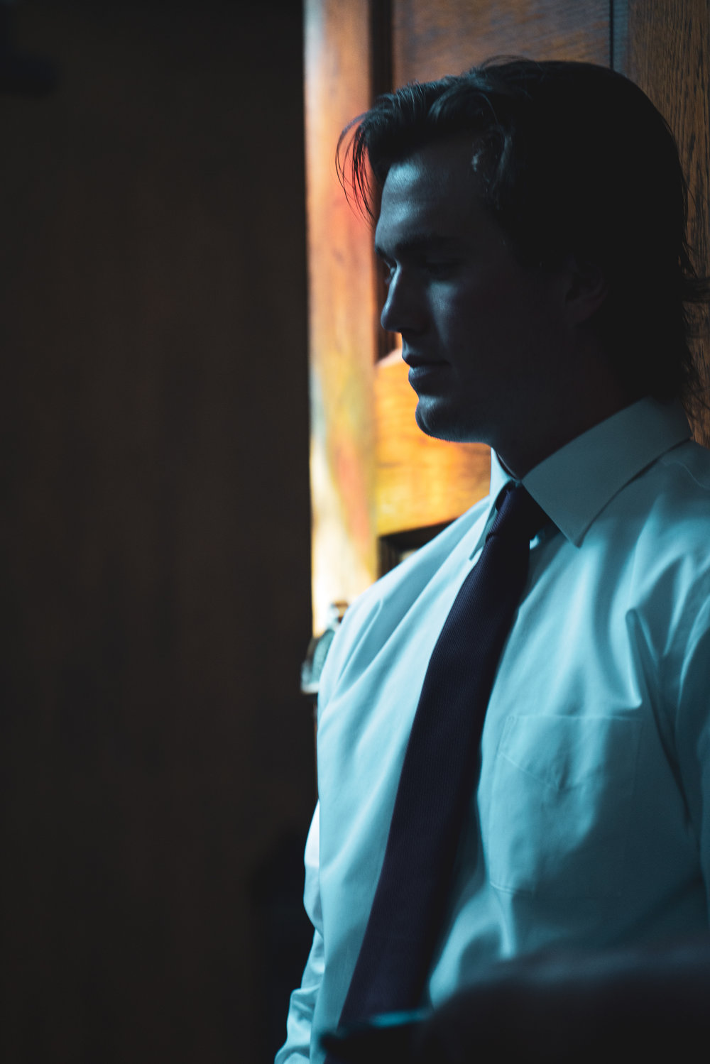 Groomsman photographed in the shadows of a Montana church.