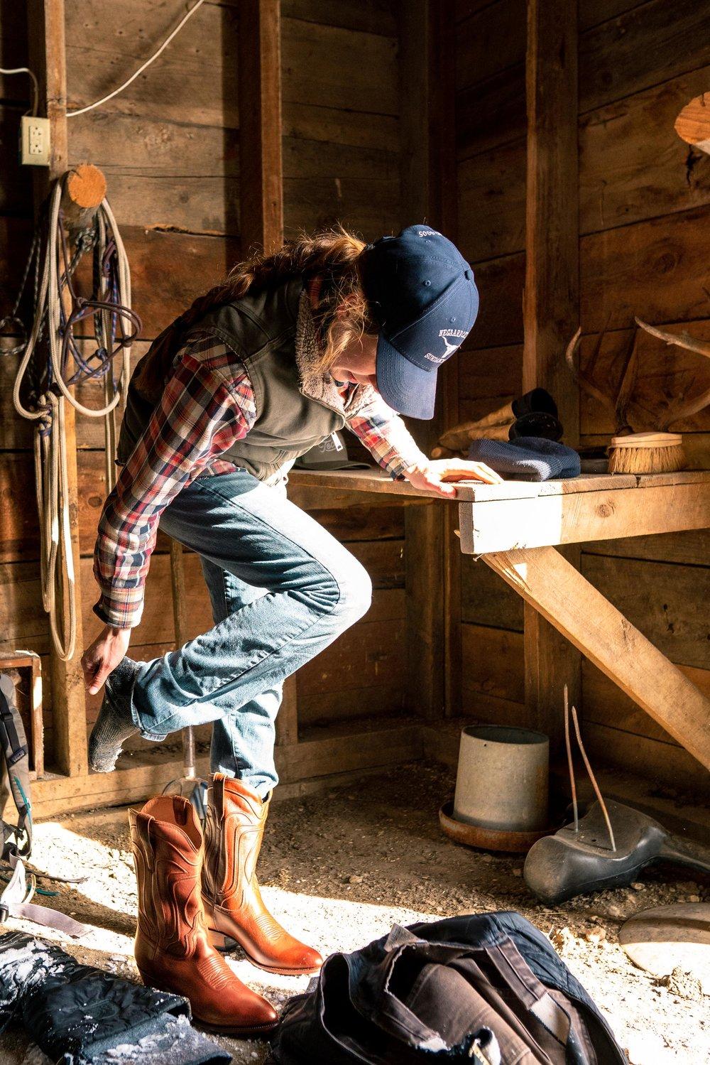 Jenna Flatgard putting Tecovas on in her barn in eastern Montana.
