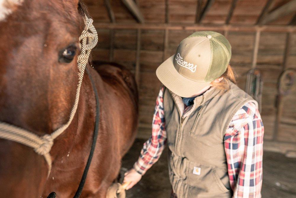 Jenna Flatgard wearing a Tecovas hat while brushing her horse in her barn in eastern Montana.