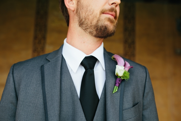 The groom in a gray suit and purple & white boutonniere