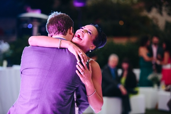 A sweet stolen moment between the bride and groom at the wedding reception